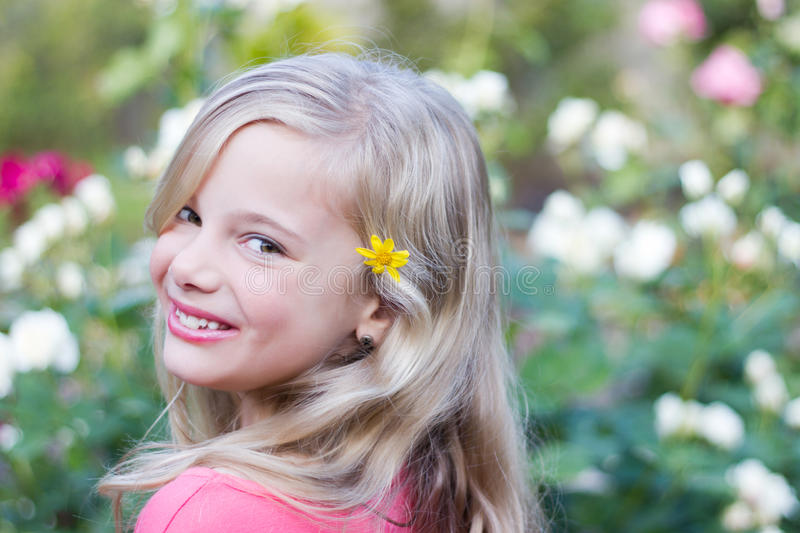 Smiling girl with flower in hair. A beautiful little girl with a bright yellow flower in her hair' spring theme stock photo