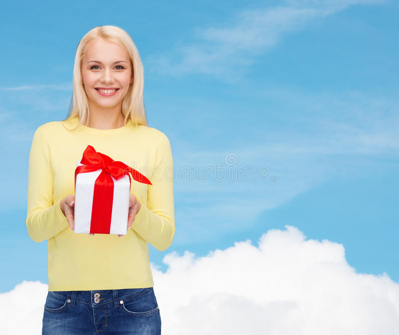 Smiling girl with gift box. Holidays, love and happiness concept - beautiful girl with gift box stock photo