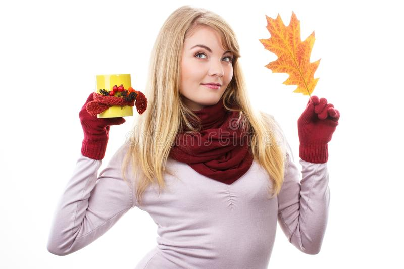 Smiling girl in gloves holding decorated cup of tea and autumnal leaf royalty free stock image