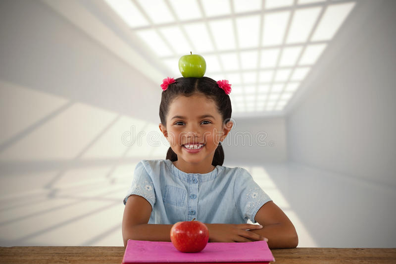 Composite image of smiling girl with granny smith apple on head stock photo