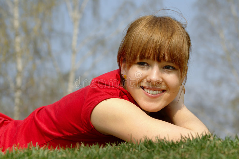 Smiling girl on grass royalty free stock photo