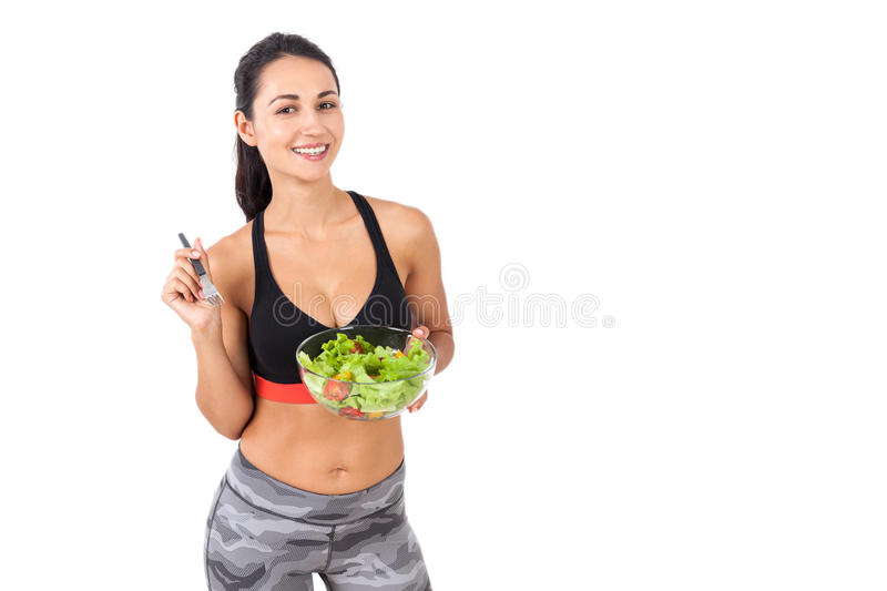 Smiling girl happily eating her salad stock images