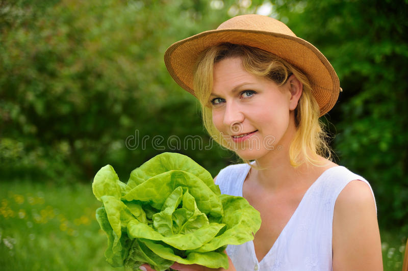 Young woman holding fresh lettuce - gardening royalty free stock image
