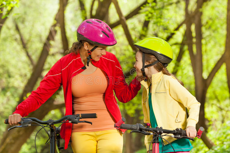 Smiling girl and her mom cycling in spring park. Smiling girl and her mom in bicycle helmets cycling at the sunny spring park stock photos