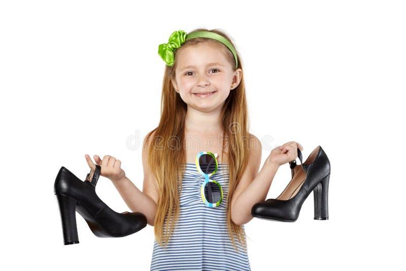 Smiling girl holding big black mother shoes. Smiling girl in striped sundress stands, holding big black mother shoes in hands royalty free stock photo