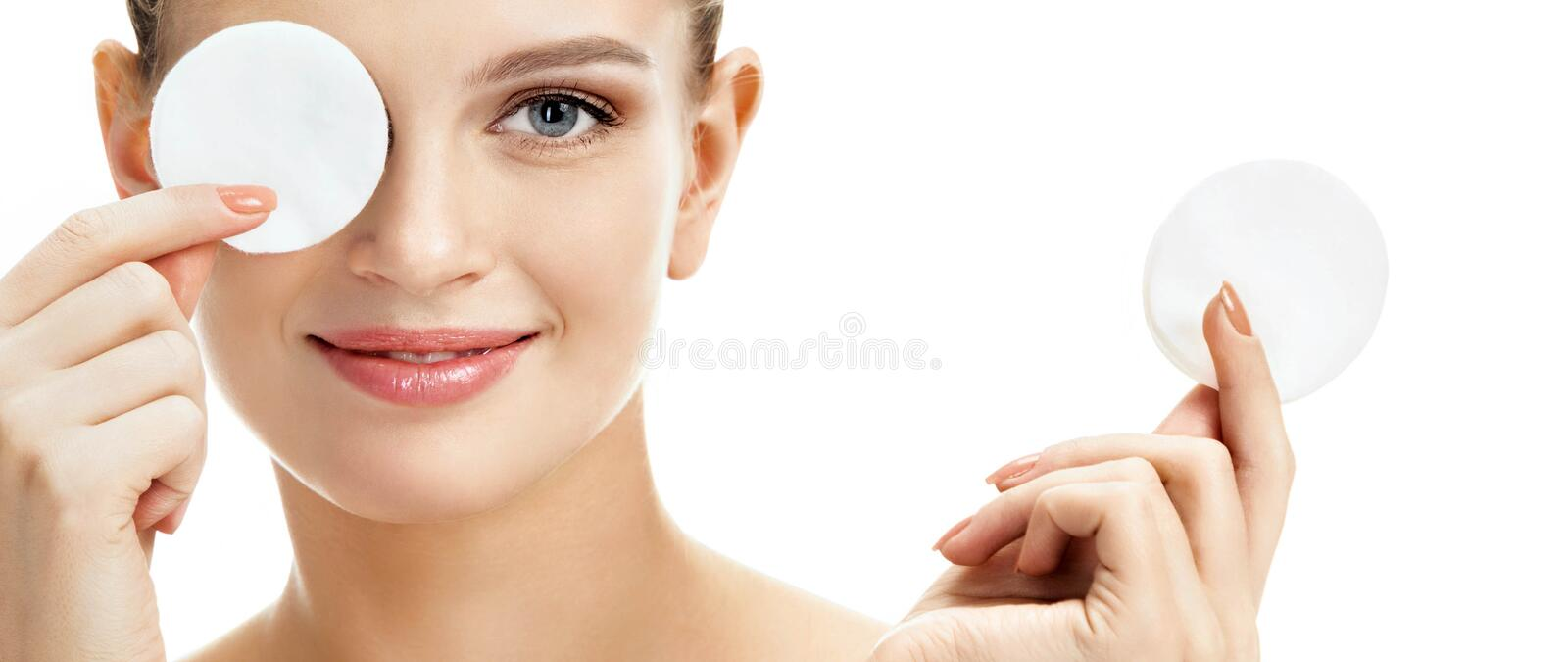 Smiling girl holding cotton pads up to her eyes. royalty free stock images