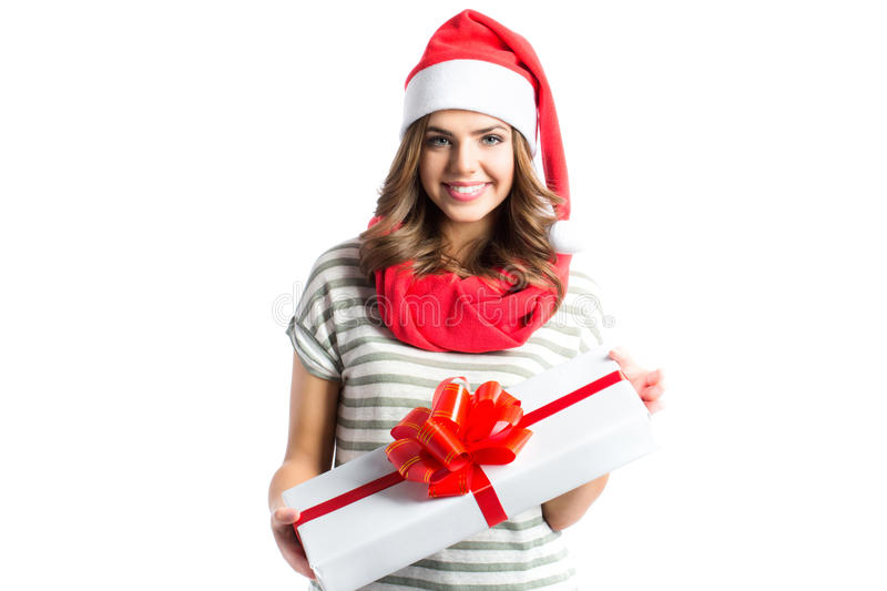 Smiling girl holding gift gifts in santa hat. stock images