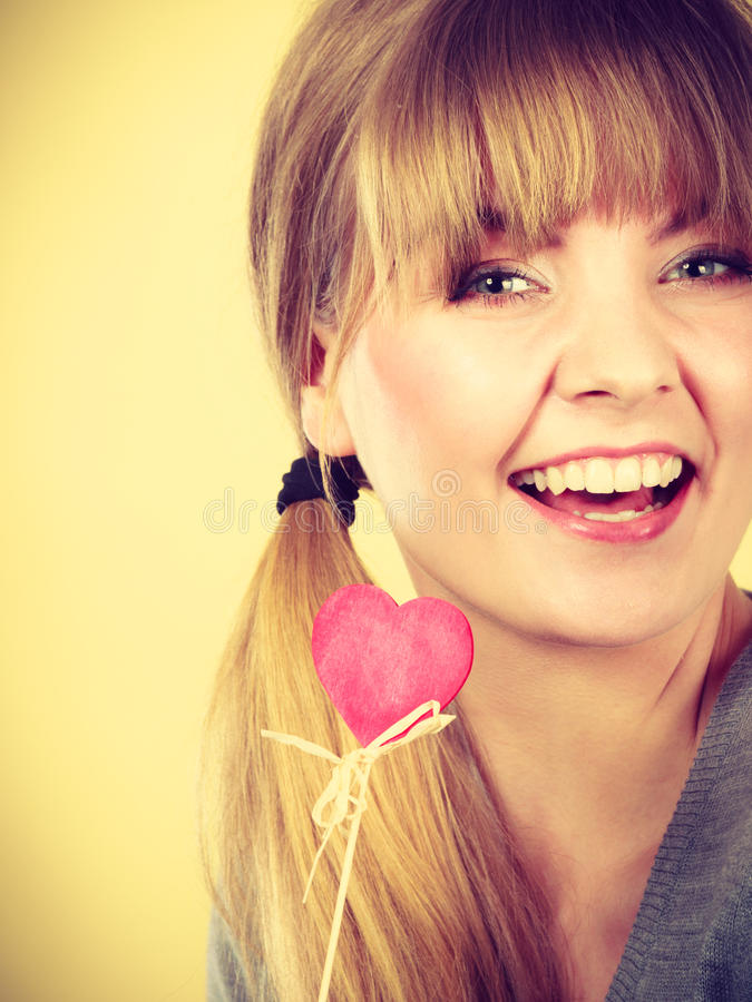Smiling girl holding heart. Love romance symbolism concept. Smiling girl holding heart. Young woman with item on stick royalty free stock photos