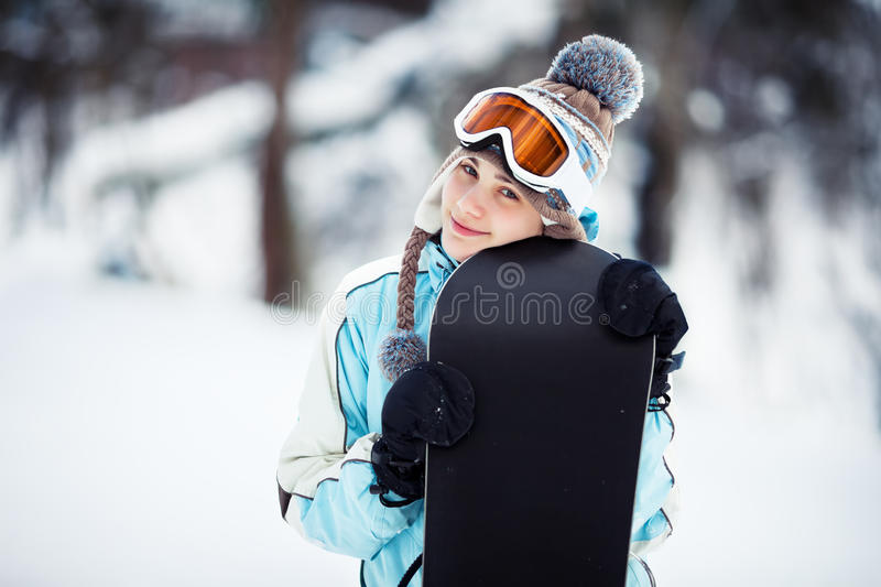 Smiling girl holding her snowboard. Young woman standing on ski slope and holding her snowboard, she's looking at camera and smiling, copy space, close up royalty free stock image