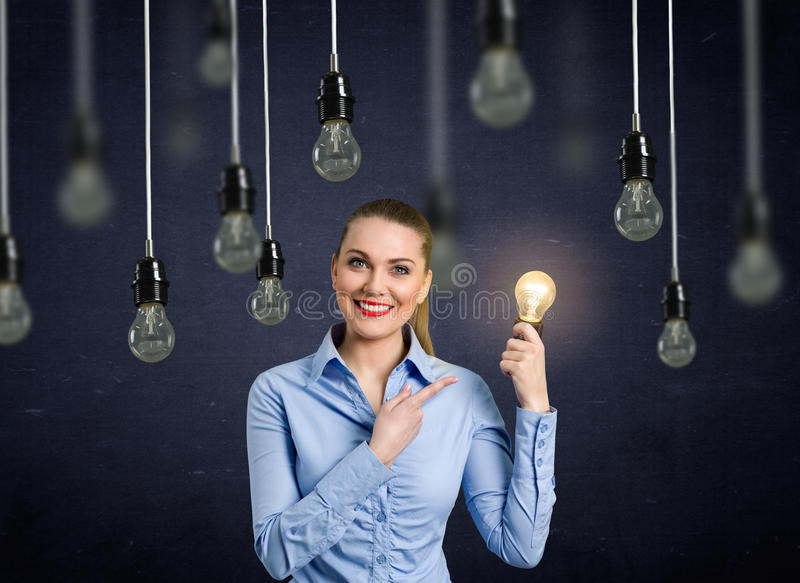 Smiling girl holding a light bulb shining royalty free stock photography