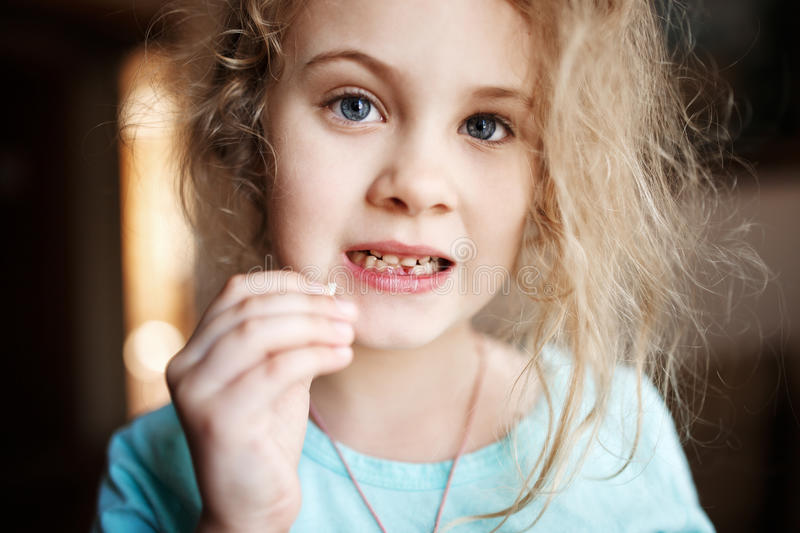 Smiling girl holding missing milk tooth, close up photo. stock images