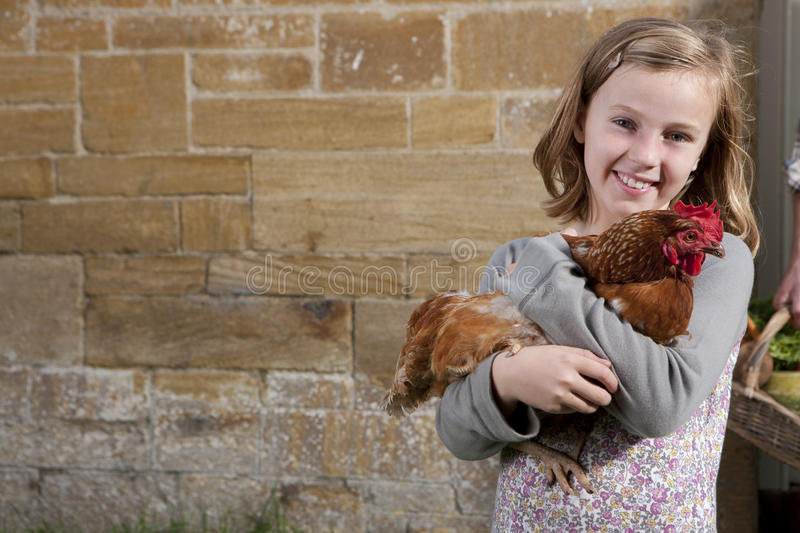 Smiling girl holding pet chicken stock image
