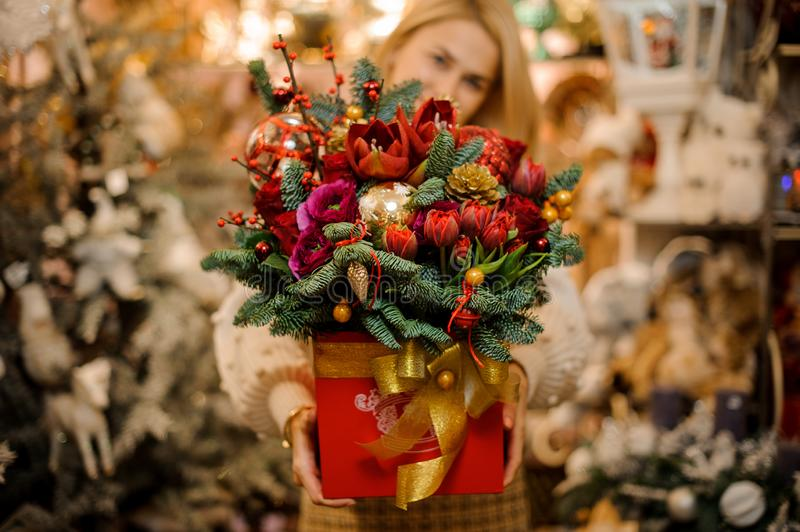 Smiling girl holding a red box with gold tape with different bright flowers decorated with fir-tree branches. In the blurred background of flower shop stock images