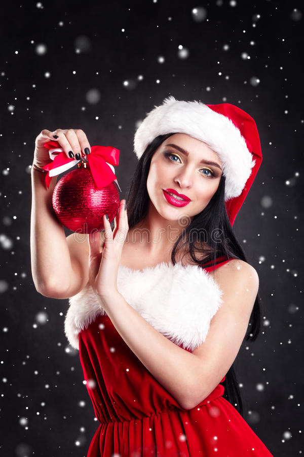 Smiling girl holding a red Christmas tree balls. Women on dress and santa`s hat. Santa`s helper .Attractive happy girl in santa h royalty free stock photos
