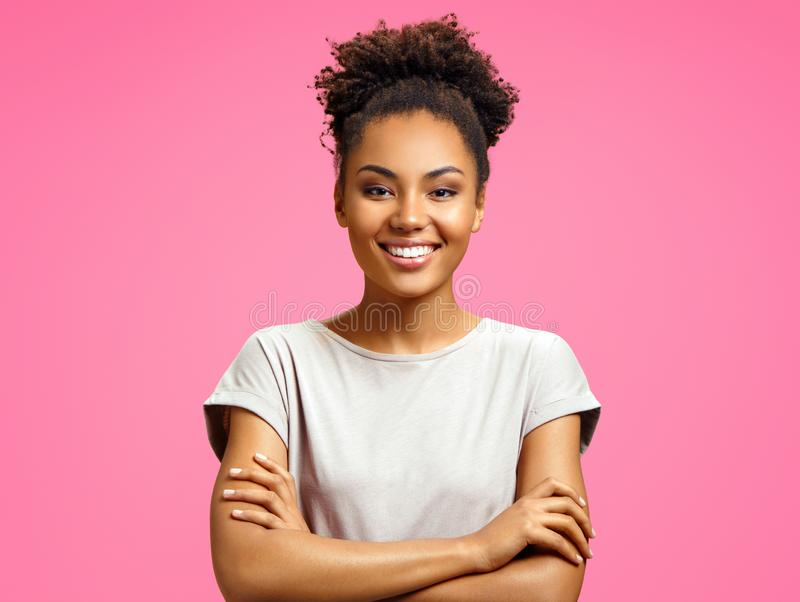 Smiling girl holds hands crossed. Photo of african american girl wears casual outfit on pink background. Emotions and pleasant feelings concept stock photos