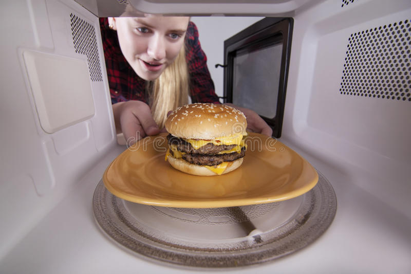 Smiling girl holds plate with a hamburger in hands. Put in microwave on turntable royalty free stock images
