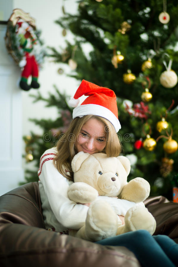 Smiling girl hugs teddy bear in christmas eve. Adorable girl in christmas cap sitting and hugging with white teddy bear. Decorated christmas tree on background stock image