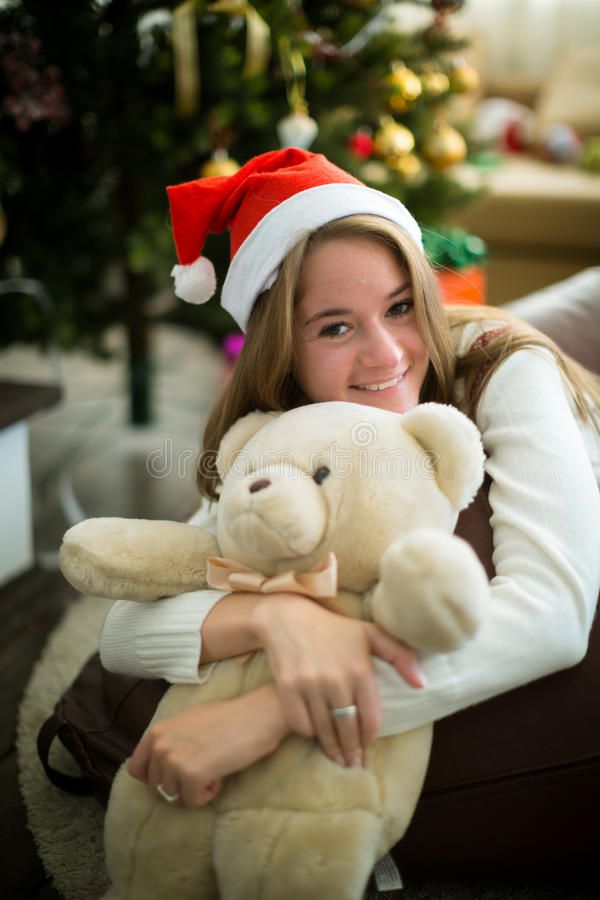 Smiling girl hugs teddy bear in christmas eve. Pretty young girl in christmas cap sitting and hugging white teddy bear. Decorated christmas tree on background stock photos