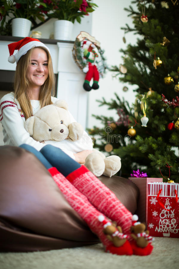 Smiling girl hugs teddy bear in christmas eve. Pretty young girl in christmas cap sitting and hugging white teddy bear. Decorated christmas tree on background stock image