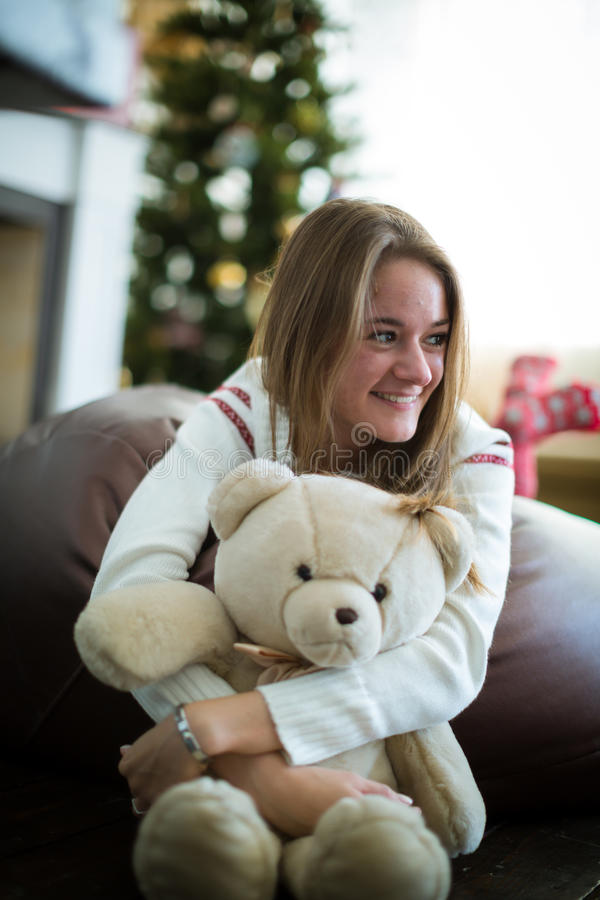 Smiling girl hugs teddy bear at christmas eve. Sensual young girl sitting and hugging with white teddy bear against decorated christmas tree stock image
