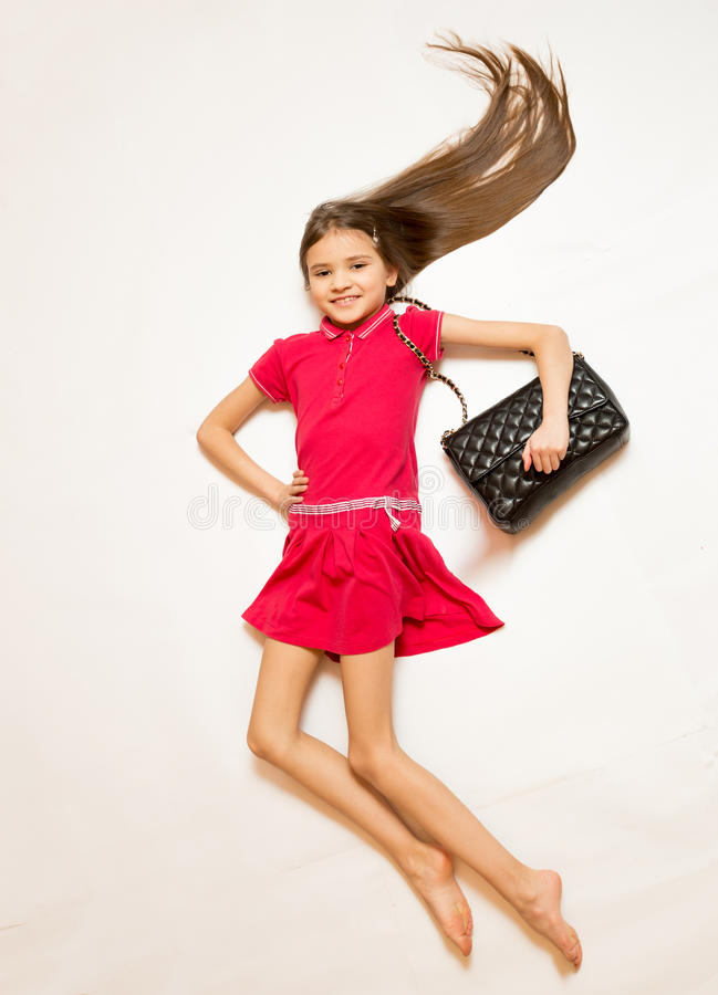 Free Smiling Girl In Red Dress And Handbag Posing On Floor Royalty Free Stock Photo - 52365765