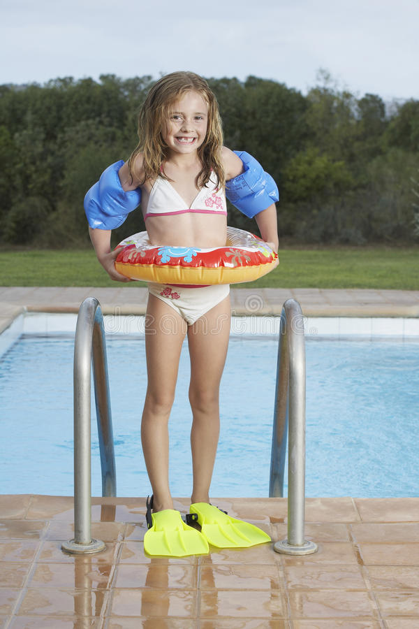 Smiling Girl With Inflatable Ring And Fins Against Pool stock photo