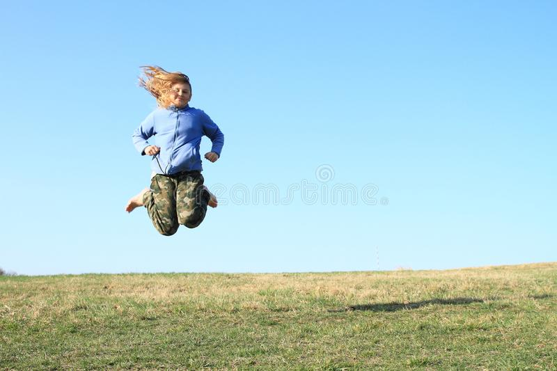 Smiling girl jumping on meadow. Smiling hairy kid - young barefoot girl with blond hair dressed in khaki pants and blue jacket jumping on grass of meadow with stock image