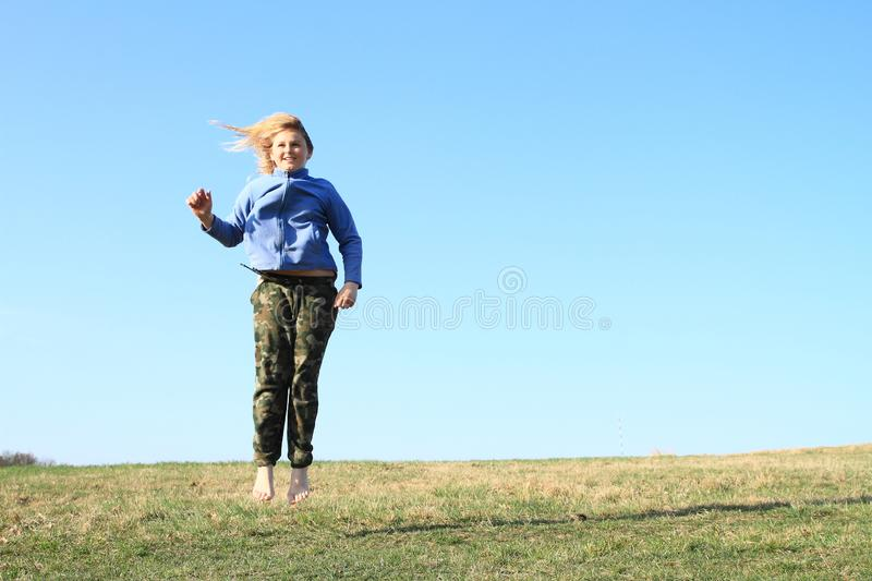 Smiling girl jumping on meadow. Smiling kid - young barefoot girl with blond hair dressed in khaki pants and blue jacket jumping on grass of meadow with clear royalty free stock photos