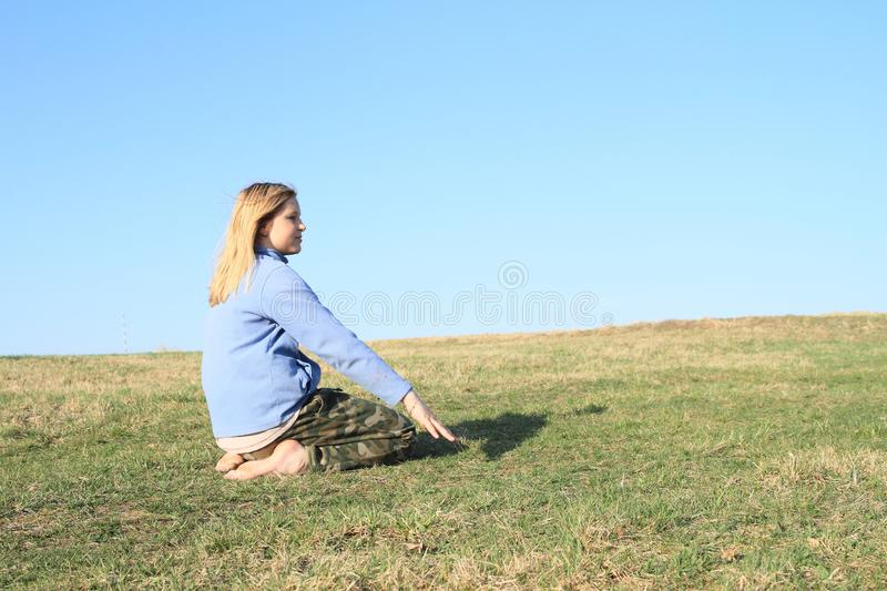 Smiling girl kneeling on meadow. Smiling kid - young barefoot girl with blond hair dressed in khaki pants and blue jacket kneeling on grass of meadow with clear stock image