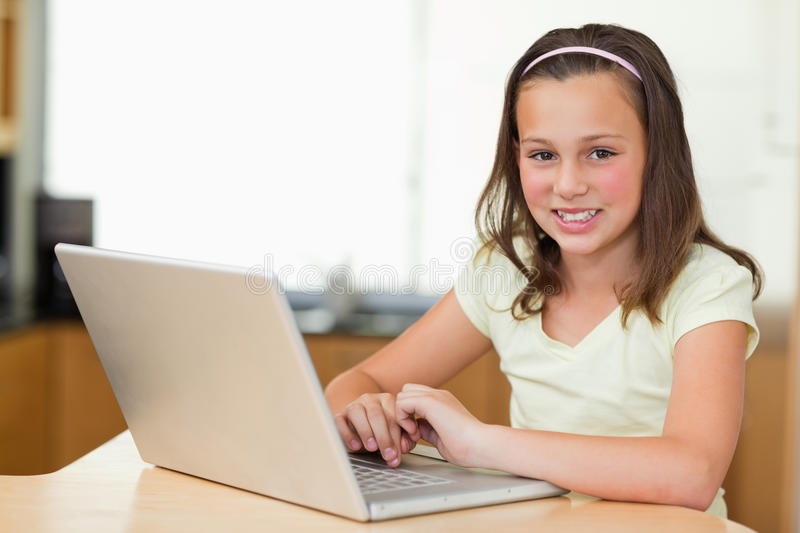 Smiling girl with laptop. In the kitchen stock photos
