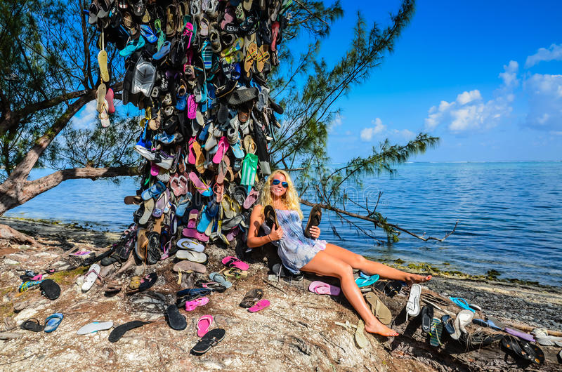 Smiling Girl Leans on Flip Flop Tree stock images
