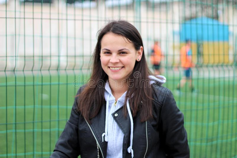 Smiling girl in a leather jacket and hoodie against the background of playing football players. Isolated, sport, woman, blue, soccer, young, fan, game stock photo