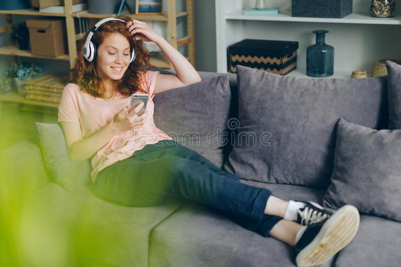 Smiling girl listening to music through headphones using smartphone at home stock images