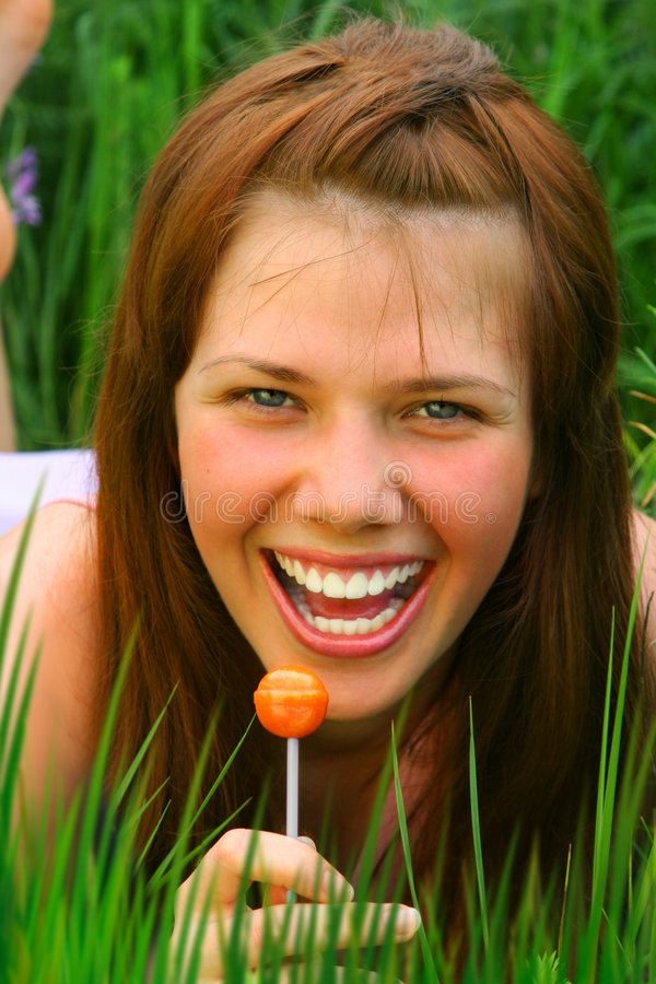 Smiling Girl with Lollipop. Smiling Girl with orange Lollipop royalty free stock photo