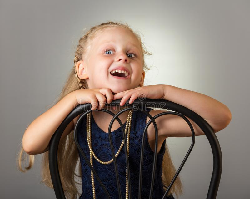 Smiling girl with long hair in dress with beads sitting on chair, on grey royalty free stock photography