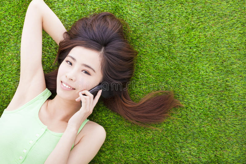 Smiling girl lying down on a meadow and talking. By smartphone royalty free stock photos
