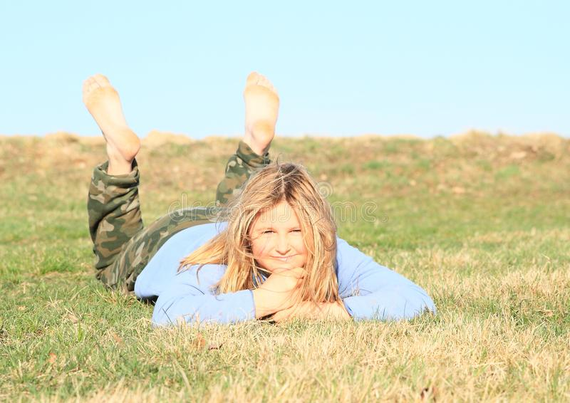 Smiling girl lying on meadow. Smiling hairy kid - young barefoot girl with blond hair dressed in khaki pants and blue jacket standing on grass of meadow with stock photos