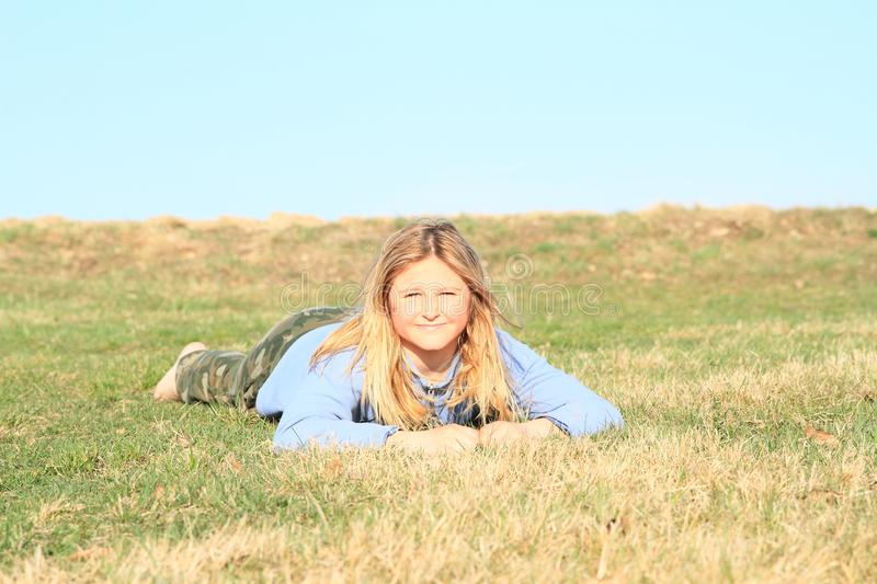 Smiling girl lying on meadow. Smiling kid - young barefoot girl with blond hair dressed in khaki pants and blue jacket standing on grass of meadow with clear stock image