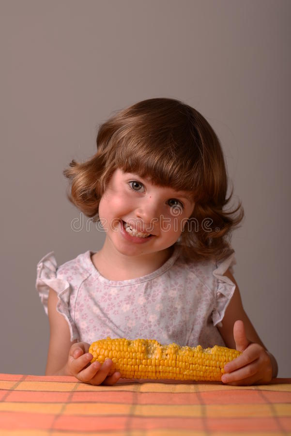 A smiling girl with maize royalty free stock photo
