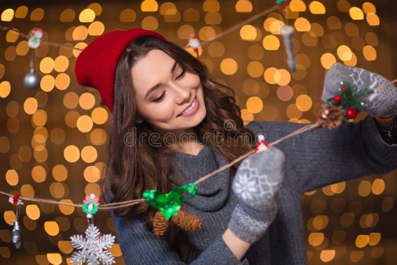 Smiling girl making handmade christmas decoration over holidays lights background royalty free stock photos