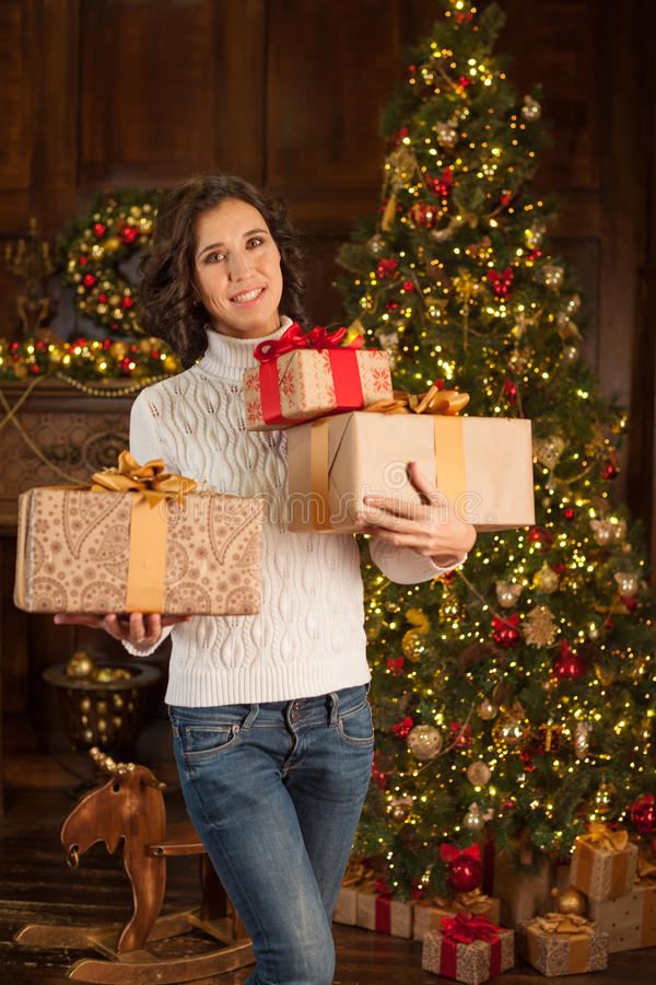 Smiling girl with many Christmas gifts stock images