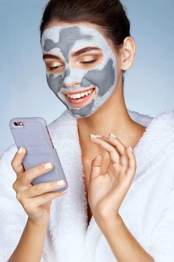 Smiling girl with mask of clay on her face stock photos