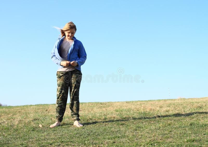 Smiling girl on meadow. Smiling kid - young barefoot girl with blond hair dressed in khaki pants and blue jacket standing on grass of meadow with clear blue sky stock photos