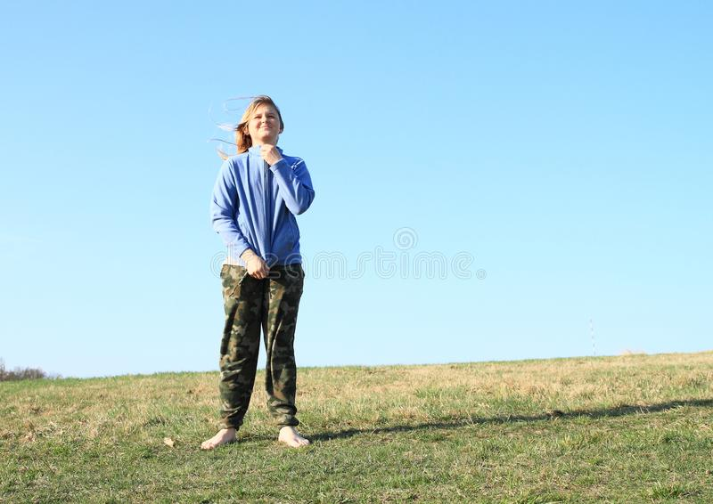 Smiling girl on meadow. Smiling kid - young barefoot girl with blond hair dressed in khaki pants and blue jacket standing on grass of meadow with clear blue sky royalty free stock photography