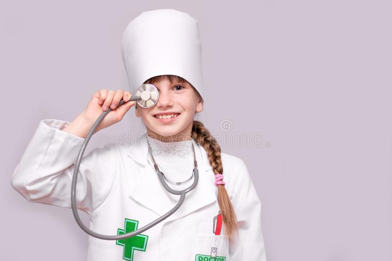 Smiling girl in medical uniform holding stethoscope and looking at camera isolated on white. Smiling little girl in medical uniform holding stethoscope and stock images