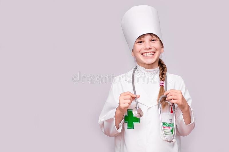 Smiling girl in medical uniform holding stethoscope and looking at camera isolated on white. Smiling little girl in medical uniform holding stethoscope and stock image