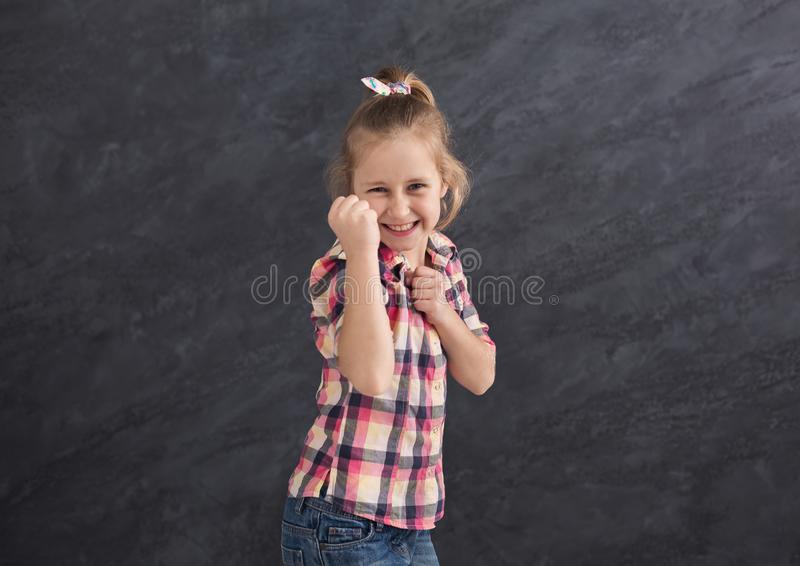 Smiling girl gesturing with fists against grey background royalty free stock photo