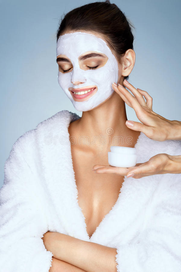 Smiling girl with moisturizing facial mask and hands of the beautician. stock photography