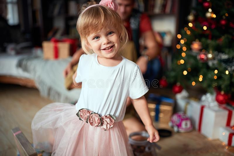 Smiling girl near the Xmas tree playing. .holidays and celebration concept royalty free stock photo