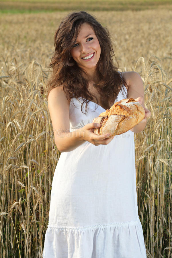 Smiling girl offering bread stock photography